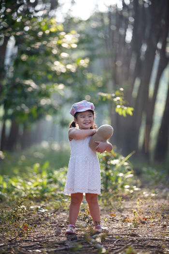 Casual Clothing Childhood Day Focus On Foreground Full Length Girls Innocence Leisure Activity Lifestyles Nature One Person Outdoors People Real People Standing Tree