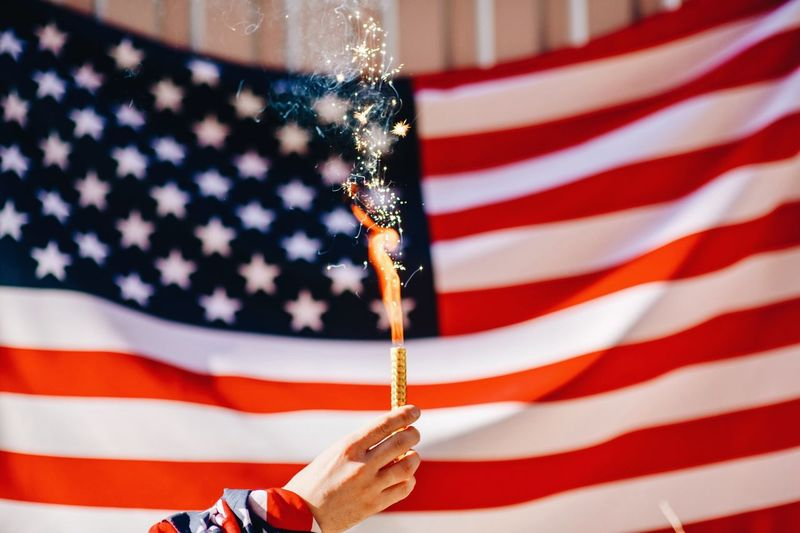 Cropped Hand Holding Lit Firework Against American Flag