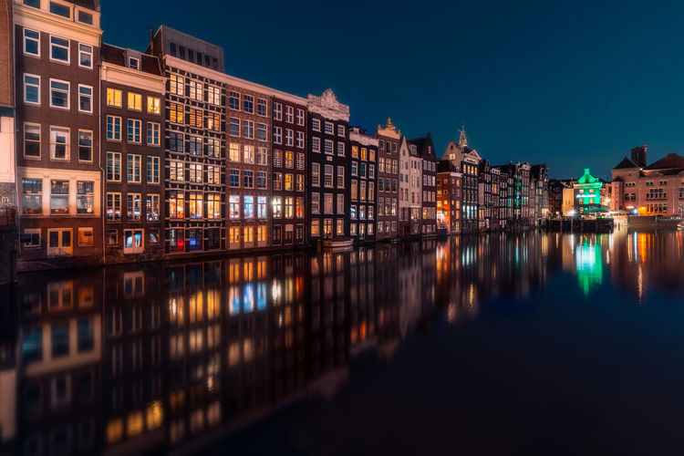Canal Amidst Buildings At Night
