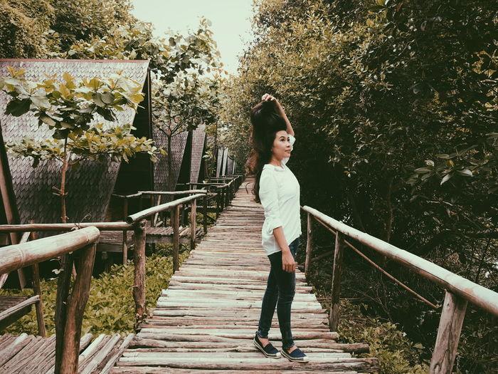Full length portrait of smiling woman standing on footbridge