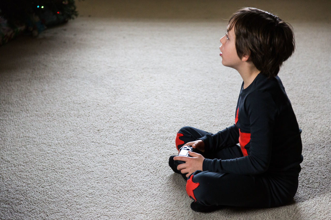 Side View Of Boy Holding Game Controller While Sitting At Home