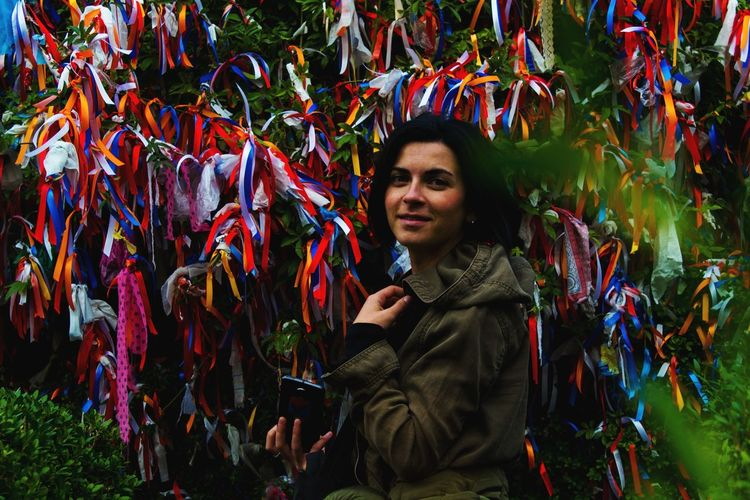 Portrait of smiling young woman standing against colorful ribbons on tree