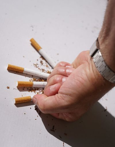 Close-Up Of Hand Crushing Cigarettes