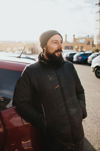 Young bearded man standing by car in city