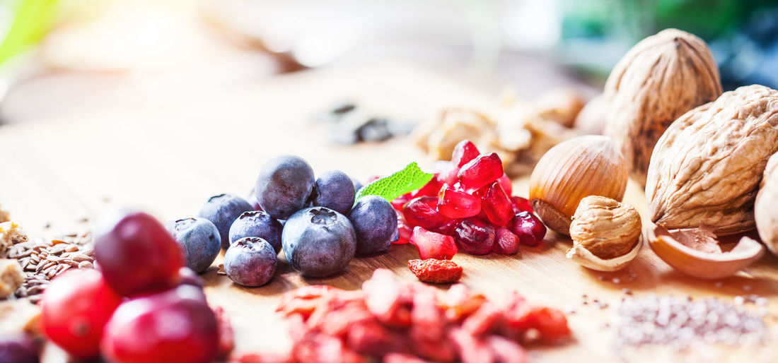 Close-up of fruits and seeds on wooden table