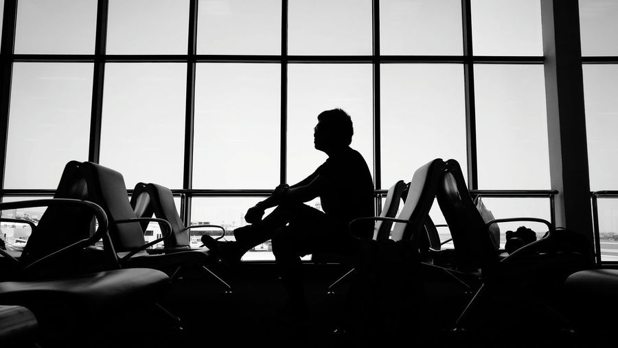 Silhouette man sitting against window at airport