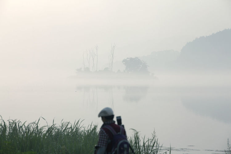 Rear view of man standing at lakeshore during foggy weather