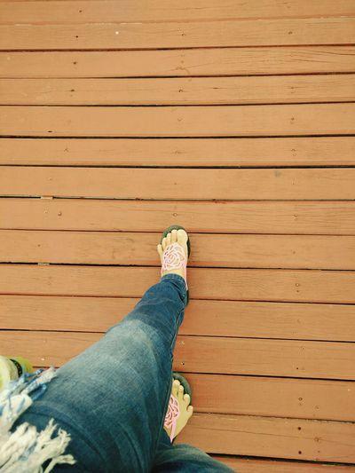Low section of woman walking on boardwalk