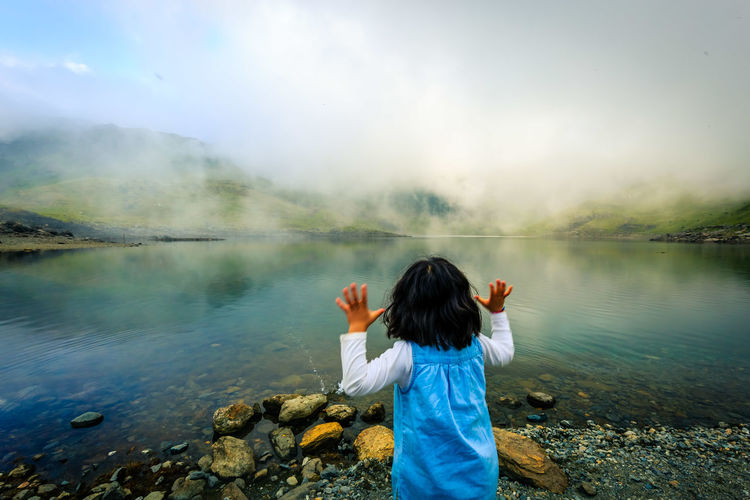 Girl standing at lakeshore during foggy weather