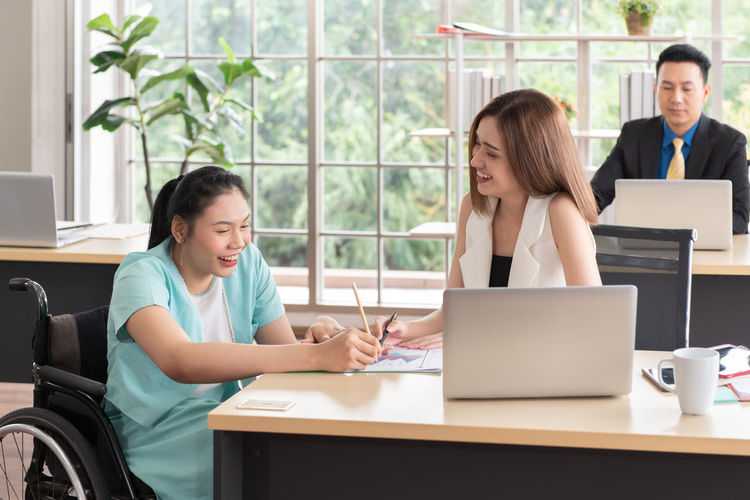 Smiling female colleagues discussing at desk in office