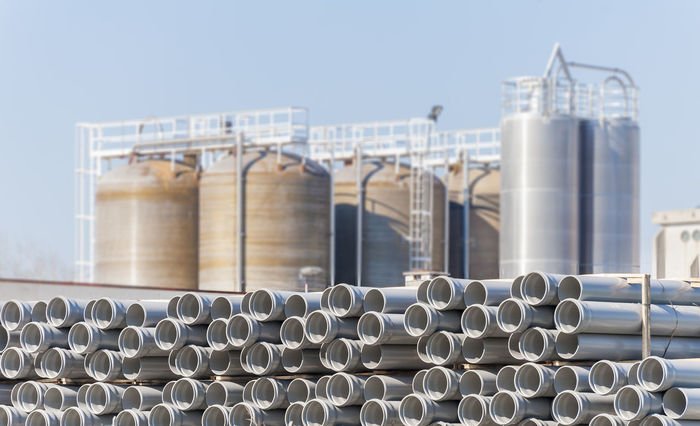 Plastic tubes for pipelines, with the background of chemical plant silos. Abundance Architecture Arrangement Built Structure Chemical Close-up Day Development Factory In A Row Industry No People Outdoors Pipe Pipe - Tube Repetition Silo Sky Tan Tubes