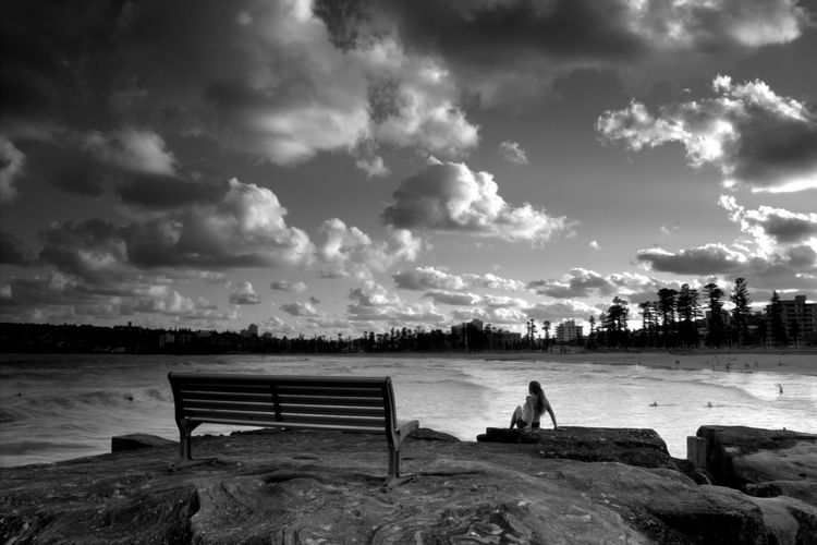 Woman Sitting At Manly Beach Against Cloudy Sky At Dusk