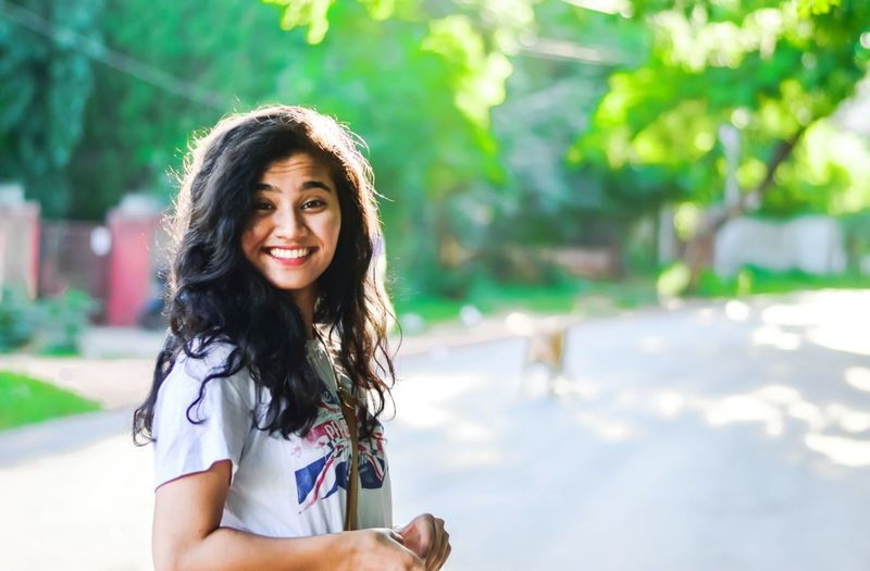 EyeEm Selects Beauty Toothy Smile Cheerful Beautiful Woman Outdoors Day Looking At Camera Long Hair Portrait Smiling Women Young Women Beautiful People Joy Close-up Sunlight Nature Curly Hair Celebration Headshot Girls Females One Person