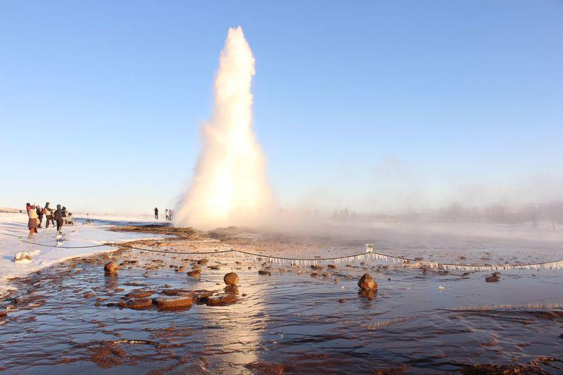 Geyser erupting against clear sky