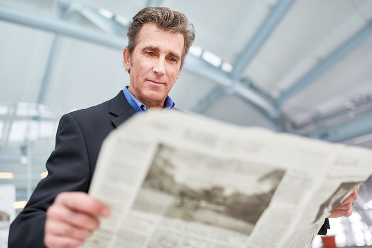 Businessman reading newspaper airport