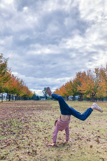 Young girl turning cartwheel in autumn leaves Autumn Balance Beauty In Nature Casual Clothing Cloud - Sky Day Field Full Length Girl Human Arm Land Leisure Activity Lifestyles Nature One Person Outdoors Plant Real People Sky Tree