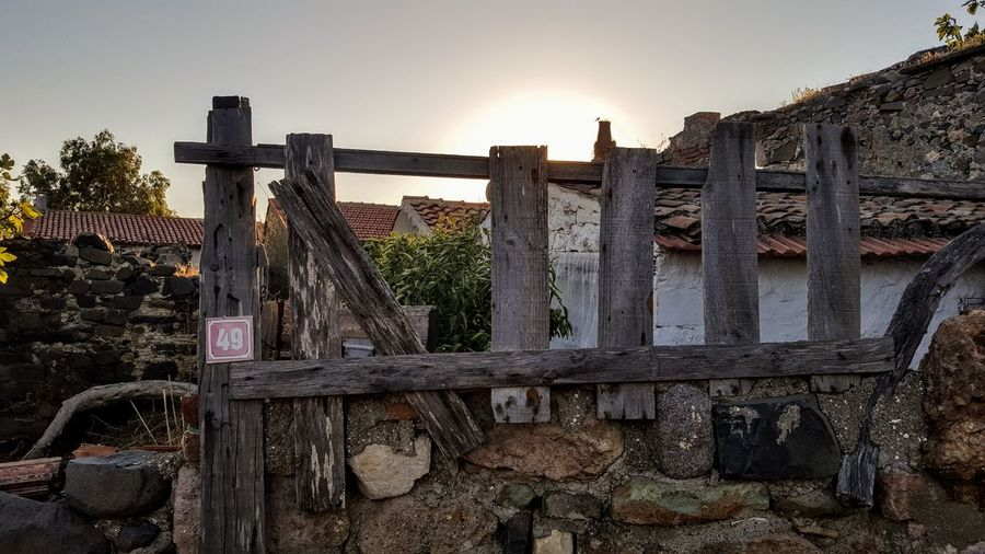 Old wooden fence against sky during sunset