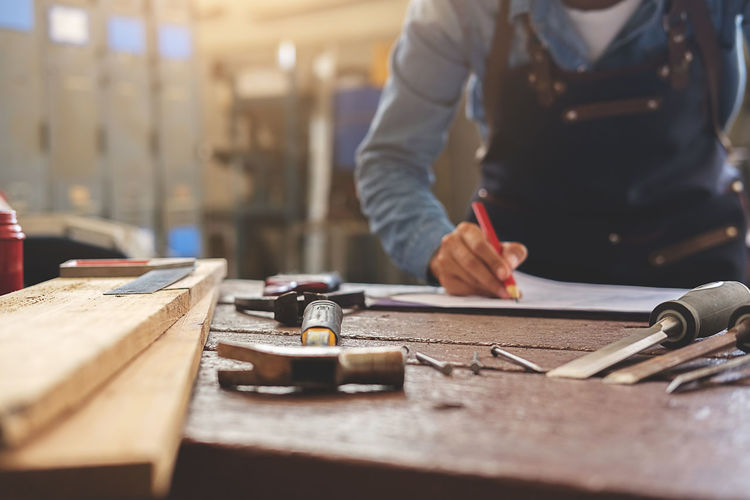 Midsection of carpenter working by tools on bench at workshop