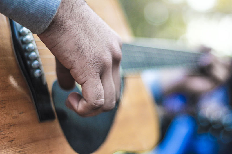 Cropped hands of man playing guitar