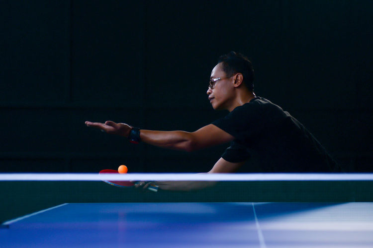 Young man playing table tennis in dark