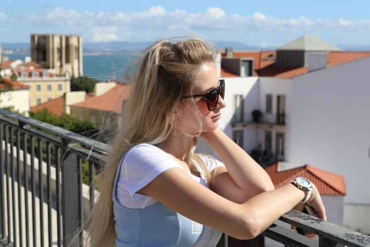 Side view of young woman wearing sunglasses on railing