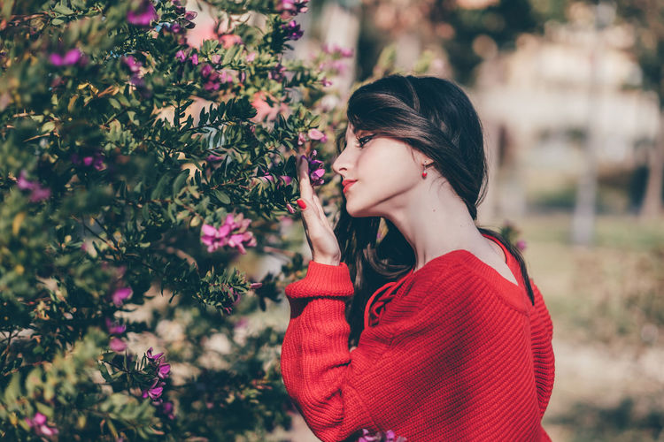 Girl in red shirt smelling flower EyEmNewHere Bookeh Flower Flowers Girl Girl Portrait Half Bust Holding Long Hair One Person Plant Purple Flower Red Red Nail Polish Red Shirt Side Shot  Side View Waist Up Women Young Women First Eyeem Photo The Portraitist - 2018 EyeEm Awards The Fashion Photographer - 2018 EyeEm Awards