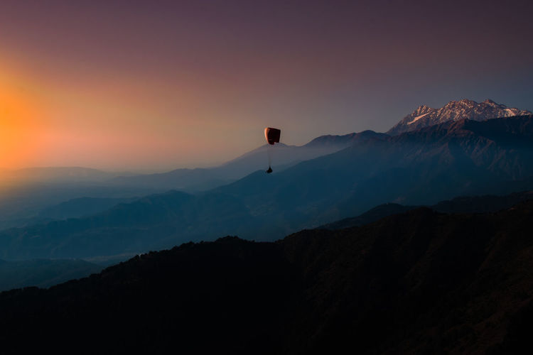 Paragliding in mountains against sky during sunset