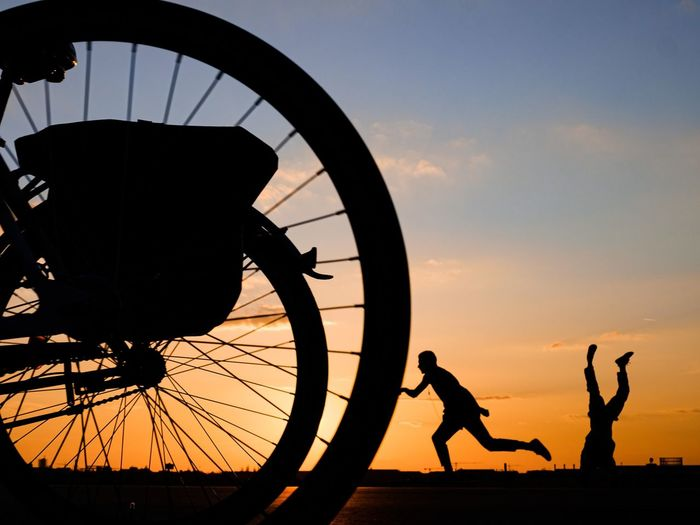 Silhouette people by bicycle against sky during sunset