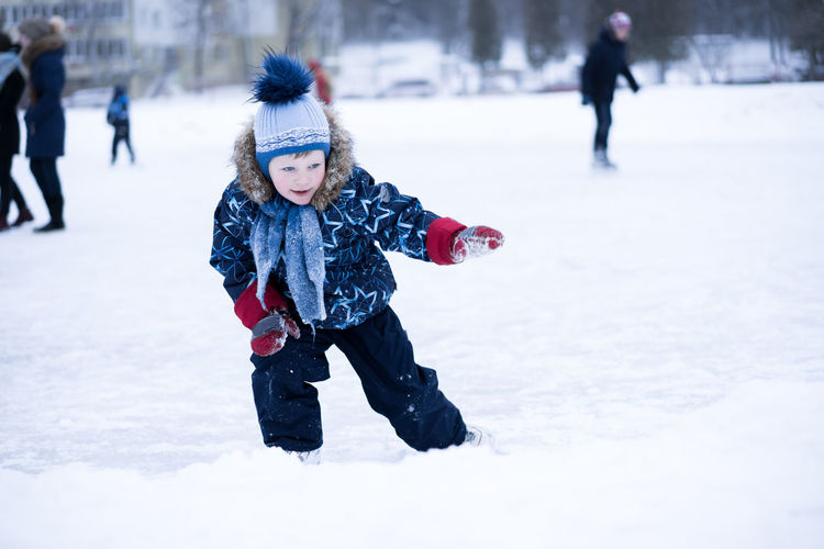 Boy in warm clothing standing on snow covered field