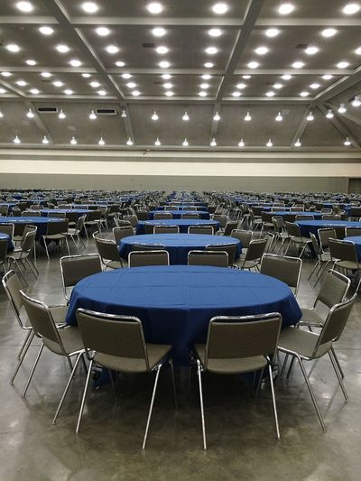 Empty tables and chairs arranged in convention center