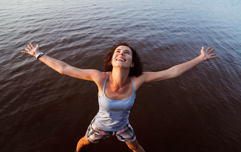 Young woman with arms outstretched in water