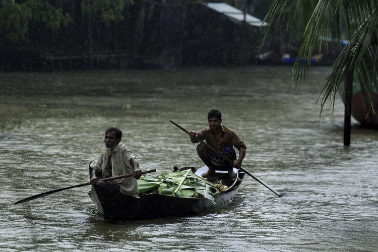 Men sitting on boat in river