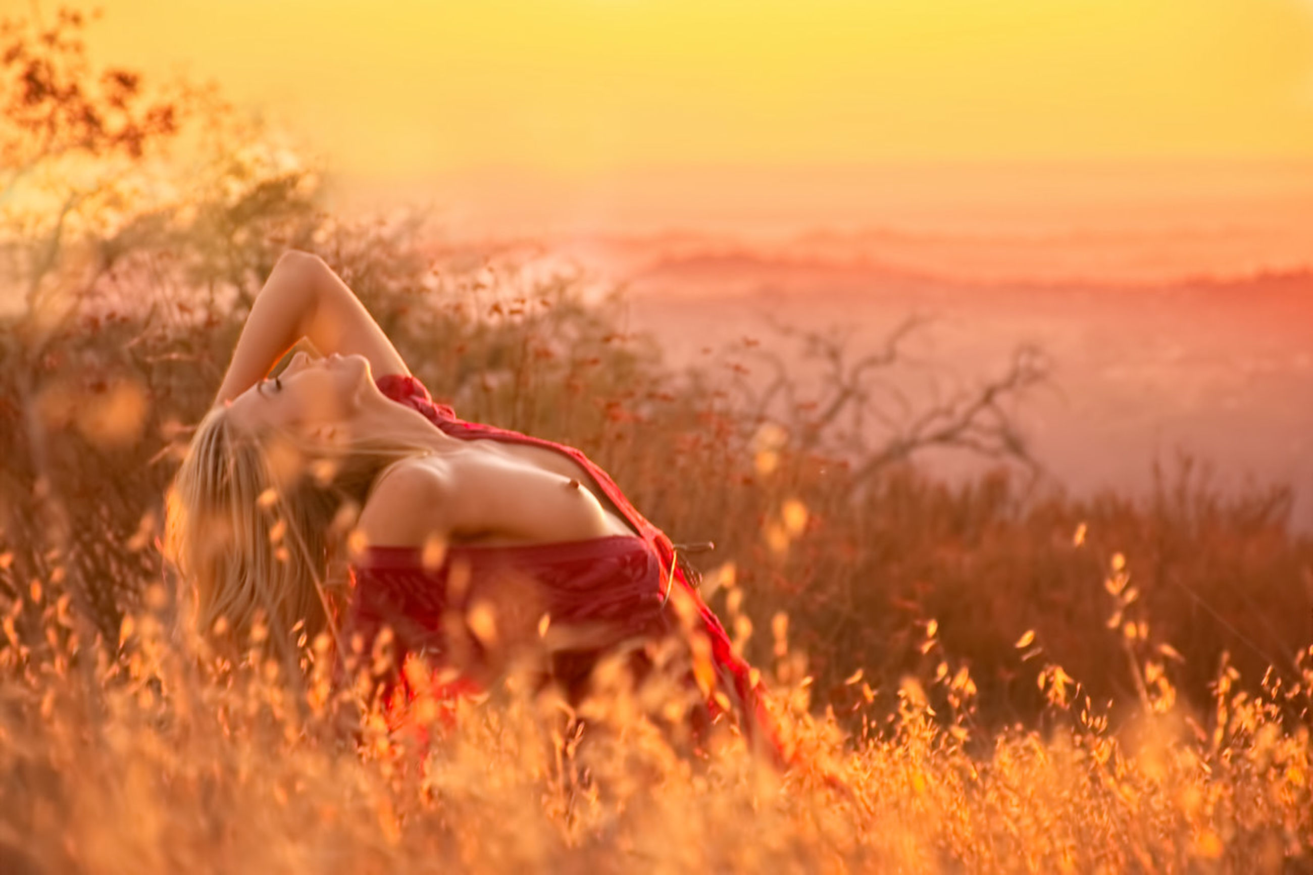 sunset, one person, land, nature, field, plant, young adult, grass, beauty in nature, sky, women, leisure activity, adult, selective focus, sunlight, relaxation, real people, lifestyles, long hair, hairstyle, outdoors, beautiful woman