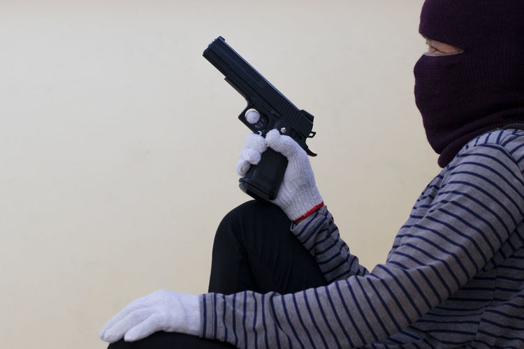 Side view of burglar holding handgun against wall