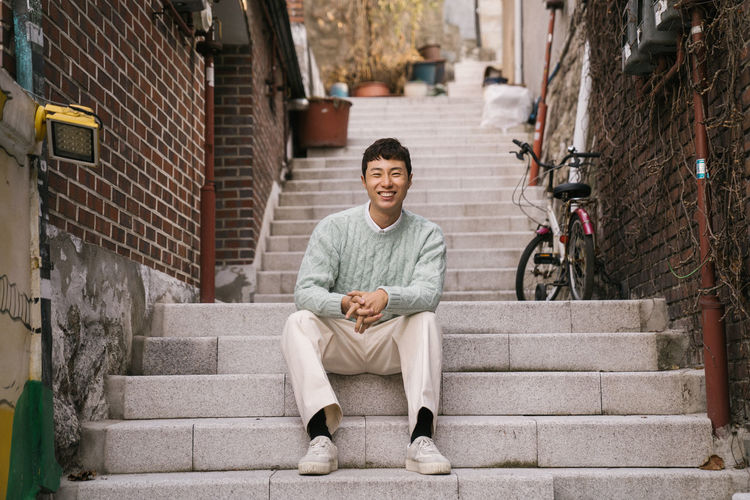 Portrait of smiling man sitting on staircase