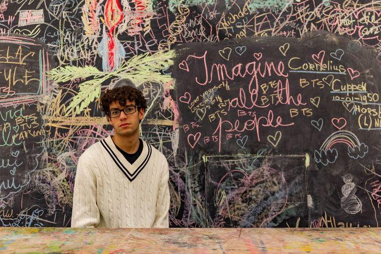 Portrait Of Teenage Boy Standing Against Blackboard