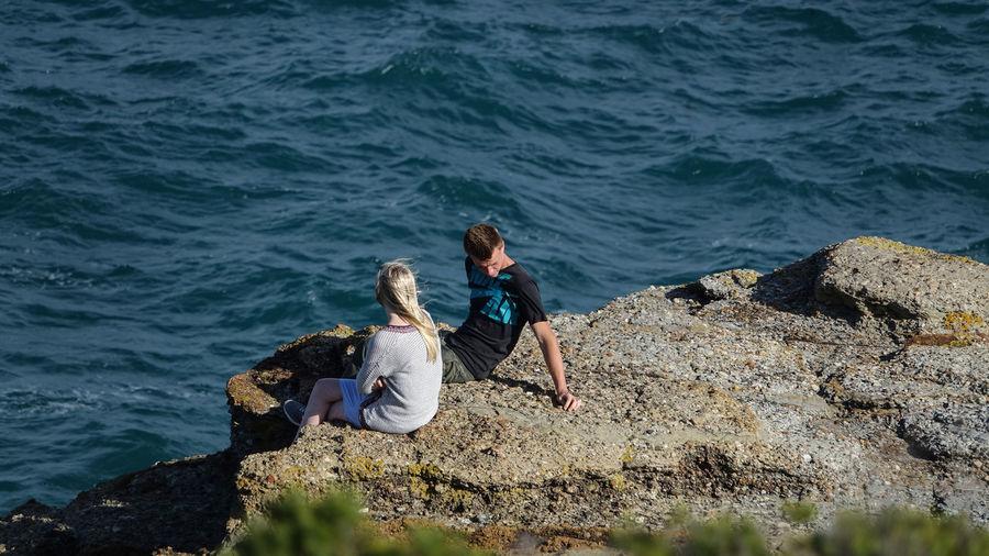 Friends sitting on rock by sea