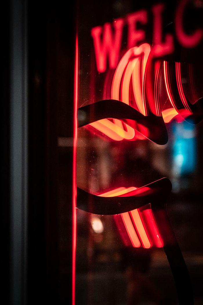 CLOSE-UP OF ILLUMINATED RED LIGHT AGAINST WINDOW