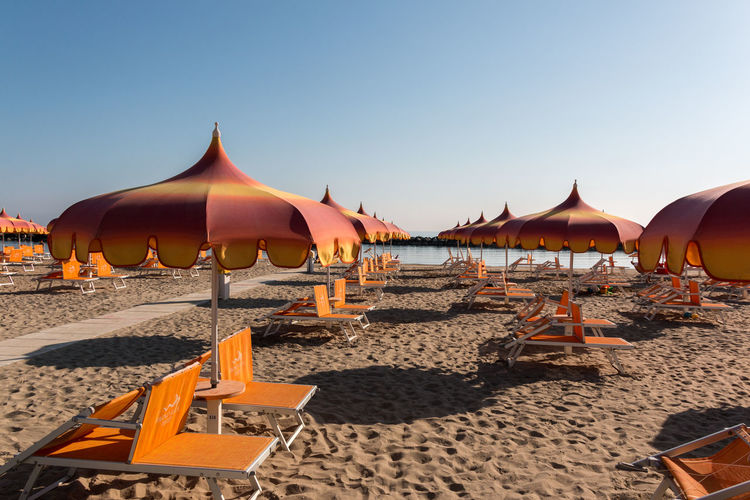 Parasols and sunbeds in Torre Pedrera near Rimini in Italy Land Sky Beach Nature Sand Sunlight Water Clear Sky Parasol Orange Color Beauty In Nature Sea Outdoors Tranquility Day No People Scenics - Nature Shadow Torre Pedrera Sandy Beach Sunshade Beach Lounger Sunbathing Seaside Resort Holiday