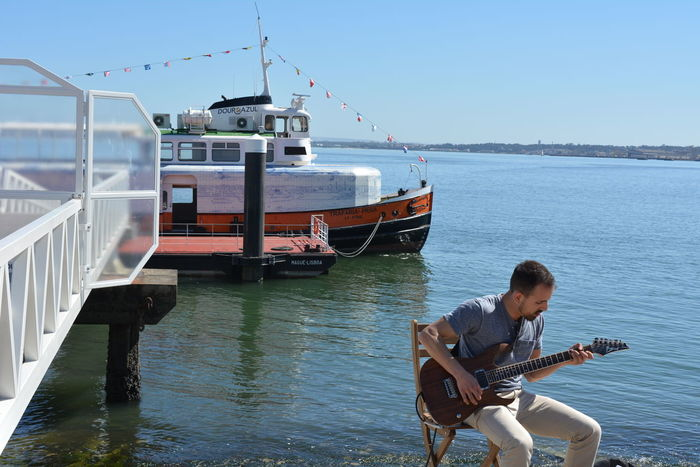 Only Men Sitting Nautical Vessel Sea Clear Sky Outdoors Musician Sky Water Day People Tejo Tejo River Lisbon Lisbon Streets Lisboa Lisboa Portugal Streetphotography Street Musician, Boats And Sea Down Town River Rio Riverside