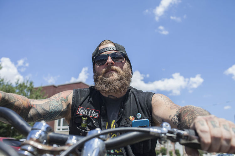 Portrait of man riding motorcycle on sunglasses against sky