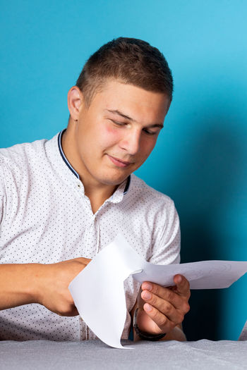 Mid adult man holding paper while sitting against wall