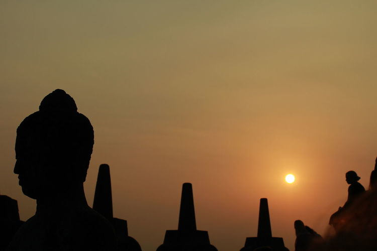 Silhouette buddha statue at borobudur temples during sunset