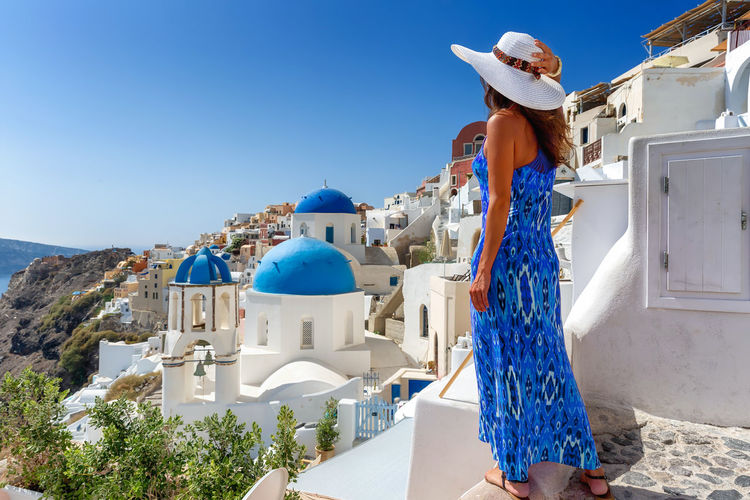 Elegant traveler woman in blue dress enjoys the view to the village of Oia, Santorini, Cyclades, Greece, during her vacation Architecture Sunlight Travel Leisure Activity White Color People Clothing Real People Building Exterior Blue Lifestyles Santorini Greece Oia Island Cyclades Village Church Dome Whitewashed Travel Destinations Tourism Tourist Traveler Travel