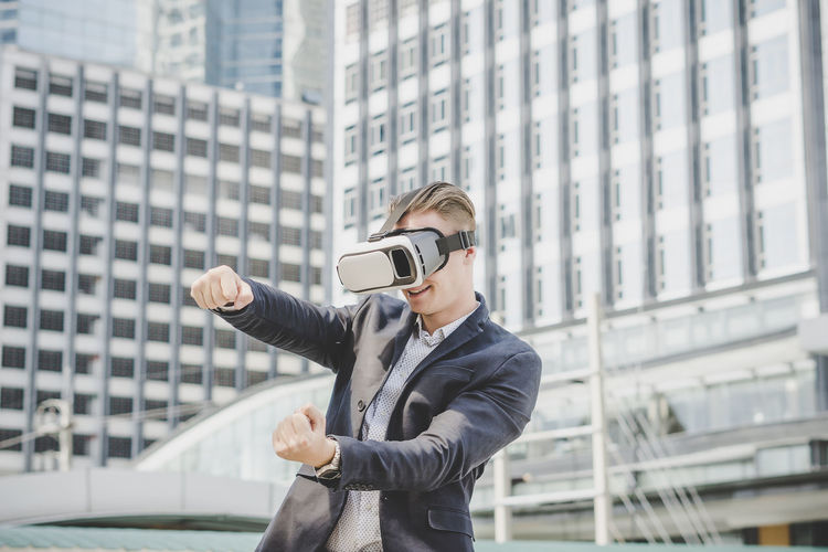 Businessman looking through virtual reality simulator while standing against building
