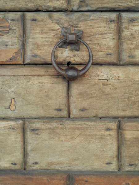Ancient wooden door detail with its door-knocker Ancient Door Ancient Wooden Door Architecture Details ArchiTexture Background Balck  Brown Door-knocker Geometry Italy Medieval Door Metal Rounded Door-knocker Old Old-fashioned Rectangle Shape Pattern Scratched And Cracked Wood Textures And Surfaces Timber Veneto Wood - Material