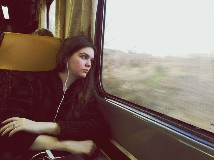 Thoughtful woman listening to music while traveling in train