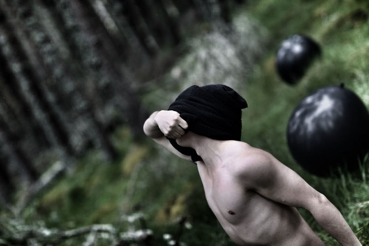 Shirtless Man Removing T-Shirt At Forest