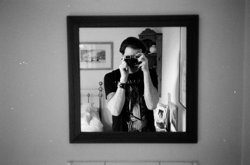 Man taking selfie through camera reflecting in mirror at home