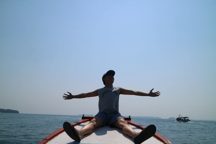 Full length of man sitting in sea against clear sky